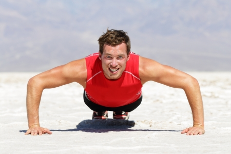 Fitness man doing push ups training outdoor in wild hot desert landscape. Determined strong male athlete doing cross fit training push up outside showing strength and determination. photo