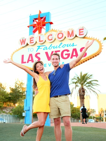 Las Vegas Sign. Couple jumping having fun in front of Welcome to Fabulous Las Vegas sign. Happy people on holidays honeymoon on the Strip, multiracial couple, Caucasian man, Asian woman, Nevada, USA. Stock Photo