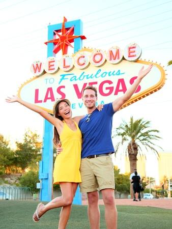 lembo: Segno di Las Vegas. Coppie che saltano divertirsi davanti Benvenuti a segno Fabulous Las Vegas. Happy persone su vacanze viaggio di nozze sulla Striscia, coppia multirazziale, uomo caucasico, donna asiatica, Nevada, Stati Uniti d'America.