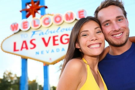 las vegas city: Las Vegas tourist couple at Las Vegas sign. Happy tourist couple taking self-portrait in front of Welcome to Fabulous Las Vegas sign. Beautiful young multi-ethnic people, Asian Woman, Caucasian man.