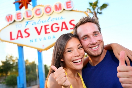 las vegas city: Las vegas couple happy and excited at welcome to fabulous Las Vegas sign billboard at the strip. Young multiracial people, Asian woman and Caucasian man having fun on travel in Las Vegas, Nevada, USA.