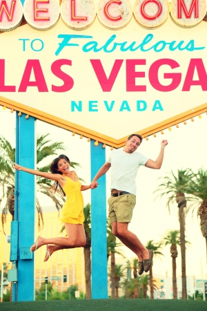 Las Vegas Sign. Happy people jumping having fun in front of Welcome to Fabulous Las Vegas sign. Beautiful young couple on the Strip cheerful and excited during travel holidays vacation, Nevada, USA. Stock Photo