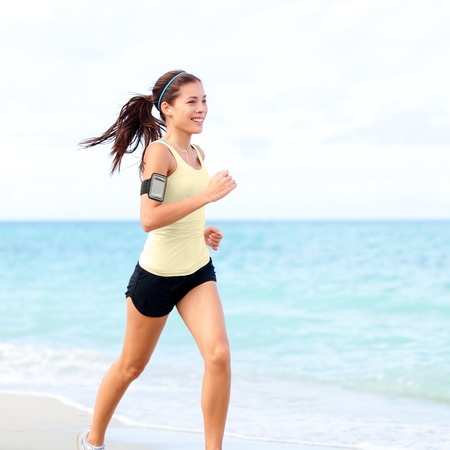 Running woman jogging on beach listening to music in earphones from smart phone mp3 player smartphone armband, Female runner training for marathon on beautiful beach. Mixed race Asian woman. photo