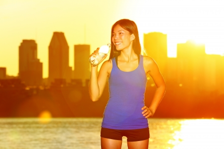 Fitness runner drinking water after city running in Montreal. Female athlete at urban skyline enjoying sun and drink from water bottle after exercising outdoor in sunshine. Asian  Caucasian girl. photo
