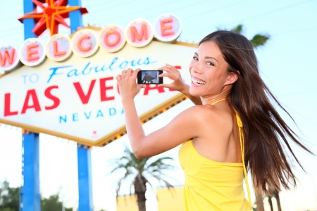 las vegas city: Las Vegas Sign tourist woman happy taking photo picture with smart phone in front of Welcome to Fabulous Las Vegas sign on the Strip. Beautiful young mixed race Asian Caucasian female model in her 20s
