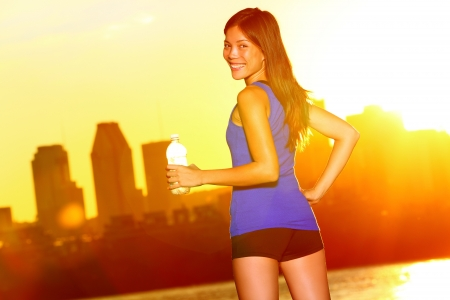 sexy asian woman: Woman Runner drinking water city running, Montreal. Female athlete looking at urban skyline enjoying sun and drink from water bottle after exercising outdoor in sunshine. Montreal, Quebec, Canada.