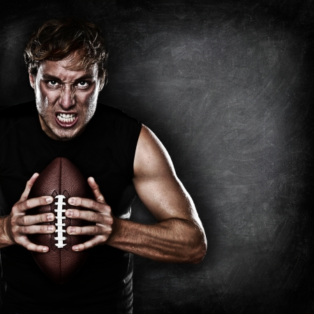 american football: Football player portrait holding american football staring aggressive looking at camera on black chalkboard background with copy space for text or design. Caucasian male model in his 20s.