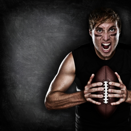 football player: Football player aggressive portrait holding american football on black blackboard background with copy space for text or design. Caucasian male model in his 20s.
