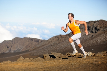 athlete: Running sport runner man sprinting in trail run. Fit male fitness sports athlete training sprint in amazing outdoor trail on volcano. Strength and success concept in compression shorts. Full body.