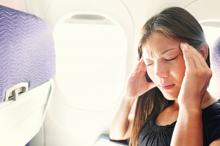 scared girl: Fear of flying woman in plane airsick with stress headache and motion sickness or airsickness. Person in airplane with aerophobia scared of flying being afraid while sitting in airplane seat.