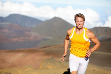 Running athlete - man runner sprinting fast. Male sport fitness model training a sprint in amazing nature landscape outdoors at speed wearing sporty runners compression clothes shorts. Strong fit man photo