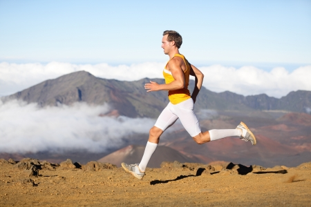 Runner man athlete running sprinting fast. Male sport fitness model training a sprint in amazing nature landscape outdoors at speed wearing sporty runners clothing compression socks. Strong fit man photo