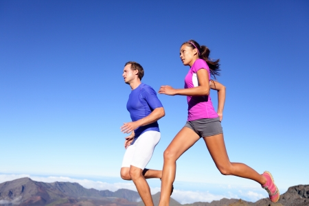 running man: Running people - Runners training outdoor. Young sports athletes couple sprinting as part of healthy lifestyle. Fit multiracial couple, Asian woman and Caucasian sports model in amazing nature.