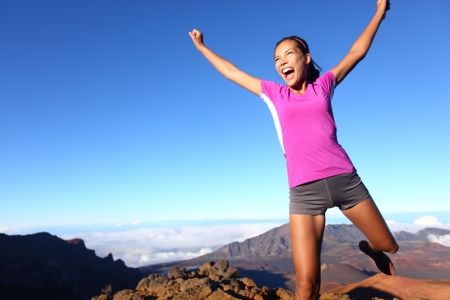 excited people: Success winner fitness runner woman jumping happy, excited and energetic with happy cheering face expression celebrating. Sporty running girl cheering after training outdoor in volcano landscape.