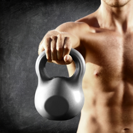 fitness model: Kettlebell dumbbell - fitness man lifting weight kettle bell training crossfit. Muscular shirtless male torso close up on blackboard background.
