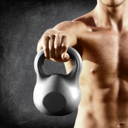kettles: Kettlebell mancuerna - gimnasio hombre de levantamiento de pesas caldera campana crossfit formaci�n. Muscular torso masculino sin camisa cerca sobre fondo pizarra.