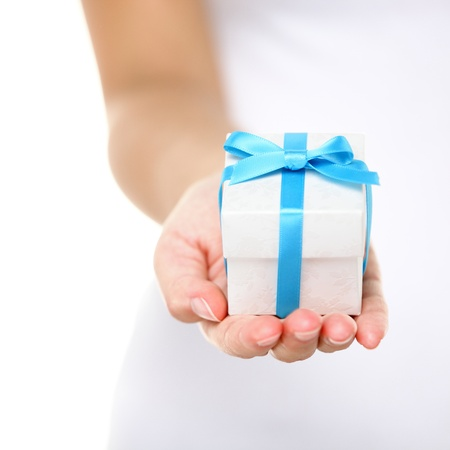 gift giving: Gift box  present or christmas gift hand close up. Decorative gift box tied with a turquoise ribbon and bow carefully cupped in female hands as she gives a surprise present to a loved one. Isolated.