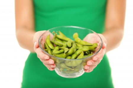Soy beans - healthy food. Woman showing healthy green fresh edamame bean.soya beans in close up isolated on white background in studio. Stock Photo