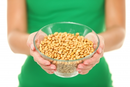 Dried salty soybeans - healthy snack. Woman showing asian snack: dry soya beans isolated on white background in studio. photo