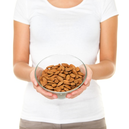 unprocessed: Almonds nuts - woman showing raw almond bowl. Healthy food concept in studio with hands lifting bowl of unprocessed almonds isolated on white background. Stock Photo