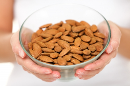 unprocessed: Almonds nuts - woman showing raw almond bowl close up. Healthy food concept in studio with hands lifting bowl of unprocessed almonds isolated on white background.