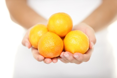 mandarin oranges: Clementine. Clementines that are a variety of mandarin oranges citrus fruits. Woman showing handful. Shot in studio with shallow depth of field isolated on white background.