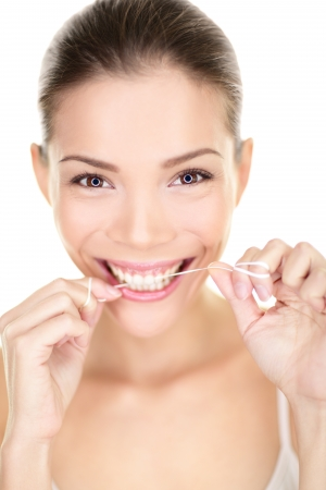 flossing: Woman flossing teeth smiling using dental flush. Happy girl with perfect teeth and toothy smile. Dental care portrait of beautiful multiracial Asian Caucasian female isolated on white background, 20s.