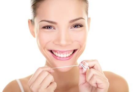 Dental flush - woman flossing teeth smiling happy with perfect teeth and toothy smile. Dental care concept with beautiful multiracial Asian Caucasian female model isolated on white background. Stock Photo