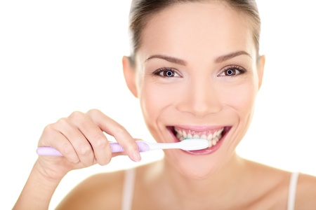 tooth paste: Woman brushing teeth holding toothbrush. Dental care close up portrait of beautiful girl brushing teeth smiling happy looking at camera isolated on white background. Mixed race Asian Chinese Caucasian