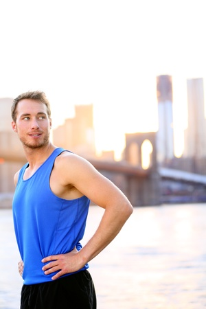 Sport athlete looking resting in New York City after running and training fitness workout outdoor in New York with Brooklyn Bridge and Manhattan skyline in background. Fit male fitness runner outside. Stock Photo - 21379838