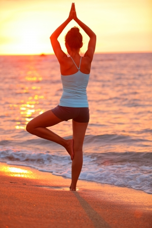 Yoga meditation woman meditating at beach sunset relaxing in yoga posture, tree pose, vrksasana. Relaxed serene Asian woman enjoying evening sun light and sunshine. From Big Island, Hawaii, USA. photo