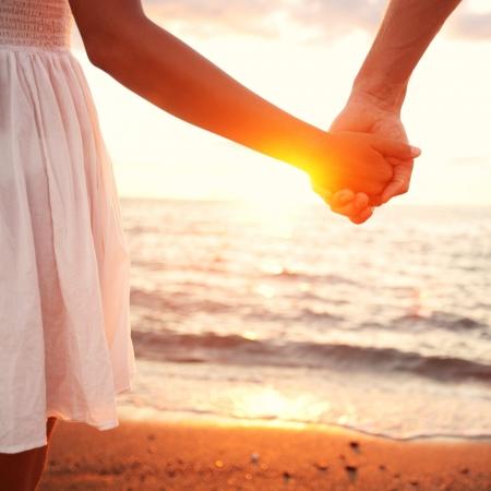 romantik: Kärlek - romantiska par håller varandra i handen, strand solnedgång. Älskare eller nygift gift ungt par i romantik på vackra solnedgången på stranden. Ung kvinna och man i kärlek gå hand i hand på stranden.