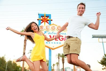luna de miel: Las Vegas Registrarse. Pareja feliz saltando. Gente que se divierte en frente de Bienvenido a la fabulosa Las Vegas signo. Hermosa joven pareja en el Strip emocionado durante las vacaciones de viaje de vacaciones, Nevada, EE.UU..