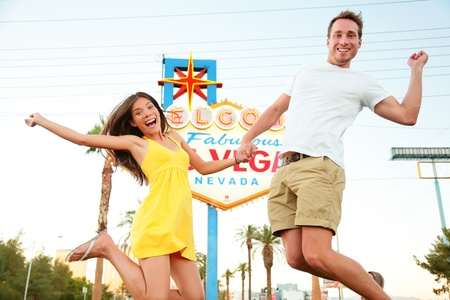las vegas city: Las Vegas Sign. Happy couple jumping. People having fun in front of Welcome to Fabulous Las Vegas sign. Beautiful young couple on the Strip excited during travel holidays vacation, Nevada, USA.