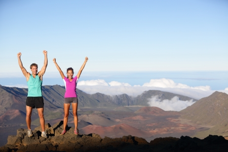 Happy cheering winning success outdoors couple excited having reached summit of mountain volcano photo