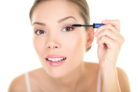 putting up: Beauty makeup woman putting mascara eye make up on eyes Stock Photo