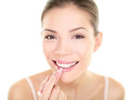 Beauty Asian girl applying color moisturizer on lips