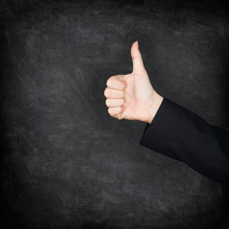 Thumbs up hand on blackboard  chalkboard background. Woman hand sign of approval and succes. Teacher or female student concept image. Black blackboard texture background icon.