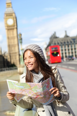 London tourist woman sightseeing holding map near Big Ben with red double decker bus. Tourism travel people concept with girl smiling happy on Westminster Bridge, London, England photo