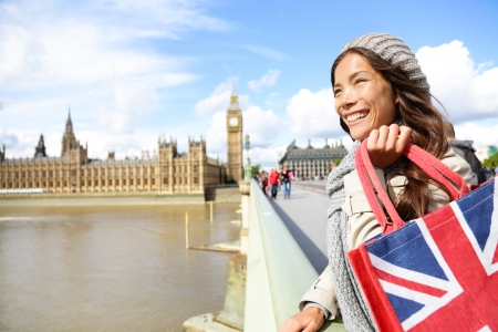 london people: London woman holding shopping bag near Big Ben. Happy woman shopper smiling happy during tourism travel vacation in London. Multicultural Asian Caucasian female traveler on Westminster Bridge.