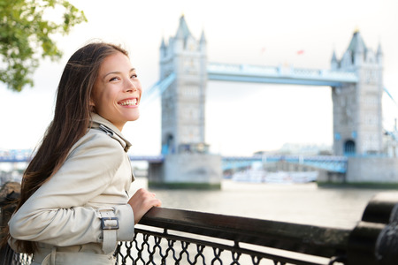 People in London - woman happy by Tower Bridge. Multicultural young professional smiling and laughing enjoying view of River Thames. Beautiful young female tourist on travel in England, Great Britain.