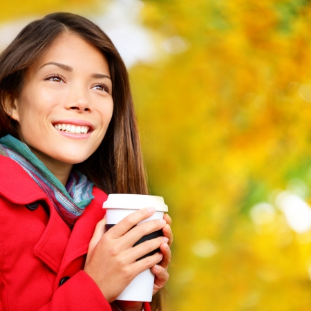 Coffee woman drinking coffee outside in fall forest. Beautiful young woman drinking hot drink from disposable paper cup outdoors in pretty autumn foliage. Multicultural Caucasian  Asian female model. photo