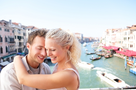 Dating couple hugging and kissing in Venice on travel vacation together. Young happy couple on holidays or honeymoon having cute romantic vacation together in Venice by Grand Canal on Rialto Bridge Banco de Imagens - 22399157