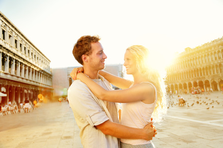 marco: Love - romantic couple in Venice on Piazza San Marco. Young couple on travel vacation holidays hugging and embracing having fun on St Marks Square, Venice, Italy. Beautiful blonde woman, handsome man