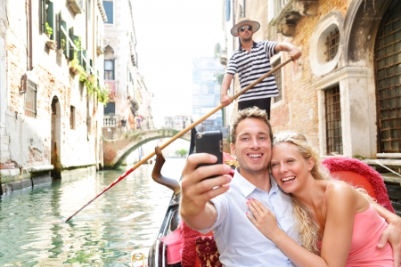 Couple in Venice on Gondole ride romance in boat happy together on travel vacation holidays. Romantic young beautiful couple taking self-portrait sailing in venetian canal in gondola. Italy. Zdjęcie Seryjne