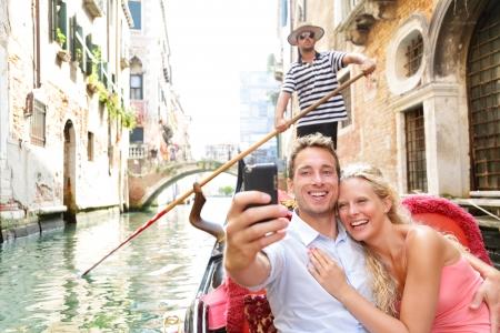 Gondole에 베니스에서 커플 여행 휴가 여행에 함께 행복 보트 로맨스를 타고. 곤돌라 베네치아 운하의 자화상 항해를 복용 로맨틱 젊은 아름 다운 부부.  스톡 콘텐츠