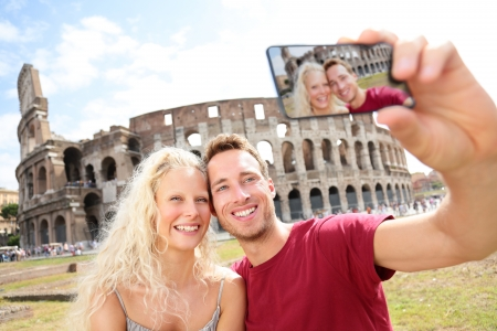 taking: Tourist couple on travel taking pictures by Coliseum in Rome. Happy young romantic couple traveling in Italy, Europle taking self-portrait with smartphone camera in front of Colosseum. Man and woman.