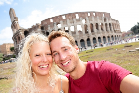 Tourist couple in Rome taking self-portrait photo by Coliseum. Happy young tourists traveling in Italy. Beautiful blonde woman and man in their 20s on holidays vacation in Europe. photo