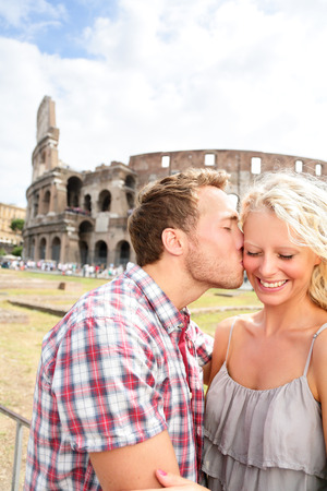 Couple kissing in love in Rome by the Colosseum. Romantic couple tourists having fun on holidays vacation and man kissing woman on cheek. Beautiful blonde girl and handsome guy. Coliseum, Rome, Italy.