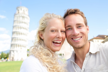 Young couple happy having fun on travel to Pisa. Tourists traveling visiting The Leaning Tower of Pisa. Beautiful laughing couple in love on romantic holidays vacation. Tower of Pisa, Tuscany, Italy. photo